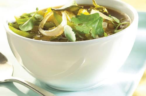 Heldere bouillon met lente-ui, peulerwten, citroen en koriander