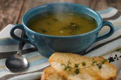 Sopa clara de verduras con vino blanco y pan al oliva.