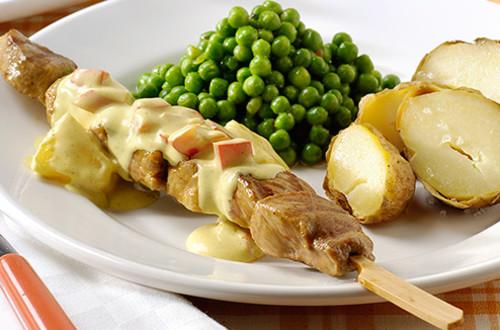 Brochettes de viande, sauce au curry, petits pois et pommes de terre soufflées