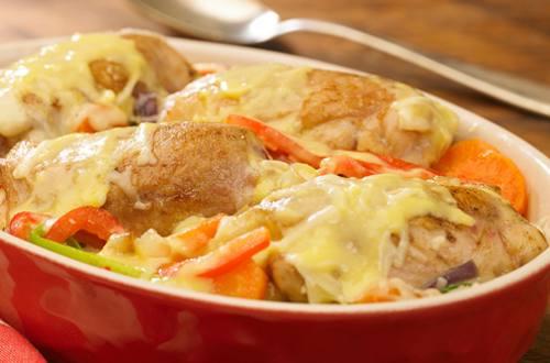 Muslos de pollo sobre colchón de vegetales cuatro quesos.