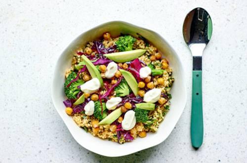 Bowl van kruiden-gierst, avocado, rode kool, broccoli en geroosterde kikkererwten