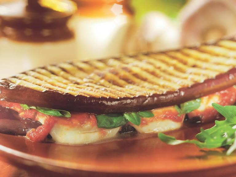 Auberginesandwich gevuld met mozzarella en basilicum