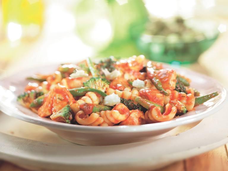 Pasta met kip, groene groenten en mozzarella in tomatensaus